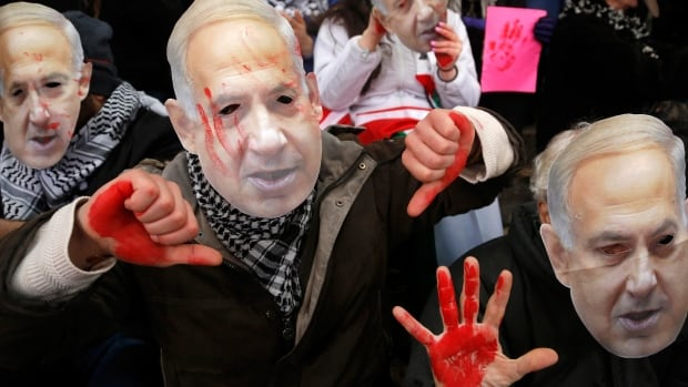 Anti-Israel demonstrators led by the protest group Code Pink wear masks of Israeli Prime Minister Benjamin Netanyahu as they sit at the entrance to the American Israel Public Affairs Committee policy conference at the Washington Convention Center on March 1, 2015.