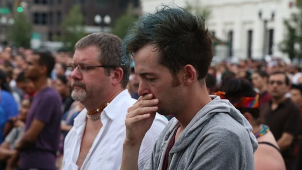 A man holds back tears at a public vigil in Orlando as a speaker recites the names of 49 people who were shot and killed early Sunday morning at Pulse nightclub.