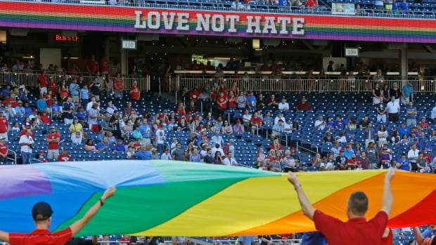 """A rainbow flag is displayed over the pitcher's mound as """"True Colours"""" is performed by the Gay Men's Chorus of Washington before a game between the Nationals and Cubs on Tuesday night in Washington, D.C."""