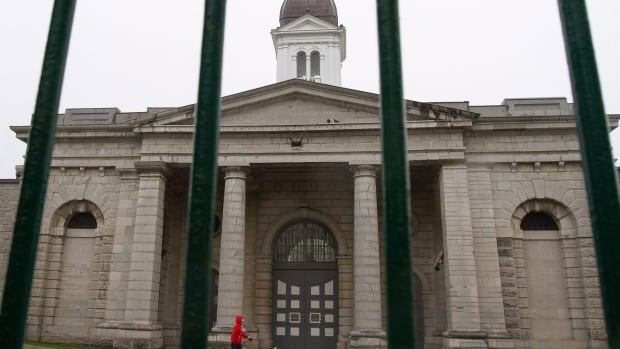 A pedestrian walks their dog in front of Kingston Penitentiary in Kingston, Ont. The notorious prison, which closed in 2013 after nearly 180 years of operation, opened up to tourists on Thursday.