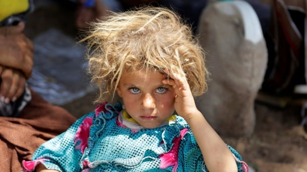 A girl from the minority Yazidi sect, fleeing the violence in the Iraqi town of Sinjar, rests at the Iraqi-Syrian border crossing in Fishkhabour, Dohuk province.