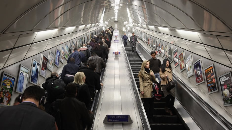 Commuters make their way on the escalator at Angel Underground station.