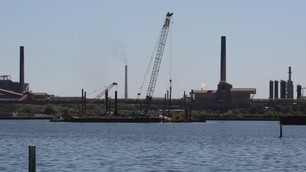A barge on the water in Hamilton Harbour works on constructing a wall around the most contaminated area of Randle Reef.