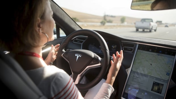 A woman demonstrates new Autopilot features in a Tesla Model S during a Tesla event in Palo Alto, California in October 14, 2015. Tesla warns drivers to keep their hands on the wheel, but its CEO Elon Musk has also tweeted videos of drivers going hands-free.