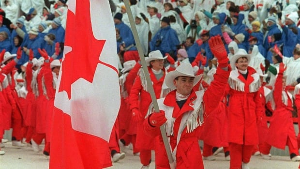 World figure skating champion Brian Orser carries the Canadian flag as he leads the Canadian Olympic team into McMahon Stadium in Calgary during the opening ceremonies of the XV Olympic Winter Games on Feb. 13, 1988.