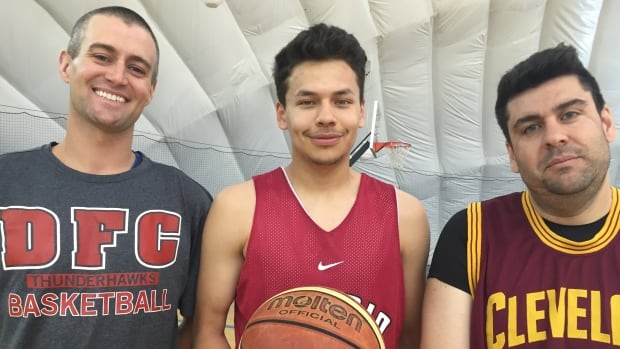 Keelan Meekis (centre) is flanked by Aaron Guthrie (left) and Alex Aiello (right) the basketball coaches at Dennis Franklin Cromarty High School in Thunder Bay.
