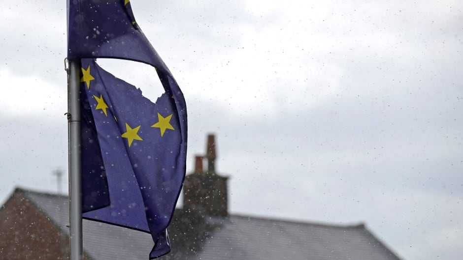 A European Union flag, with a hole cut in the middle, flies at half mast outside a home in Knutsford, Cheshire on June 24, 2016. The results from the historic EU referendum have now been declared and the United Kingdom has voted to leave the European Union.