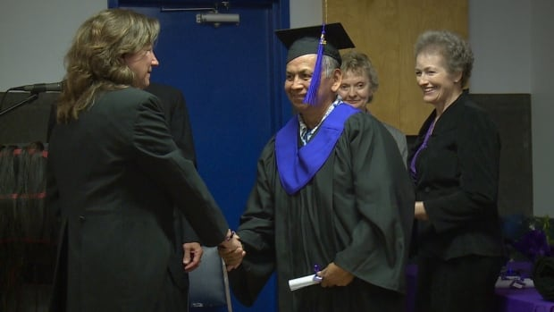 Andrew Harvey smiles as he officially graduates high school at age 62.