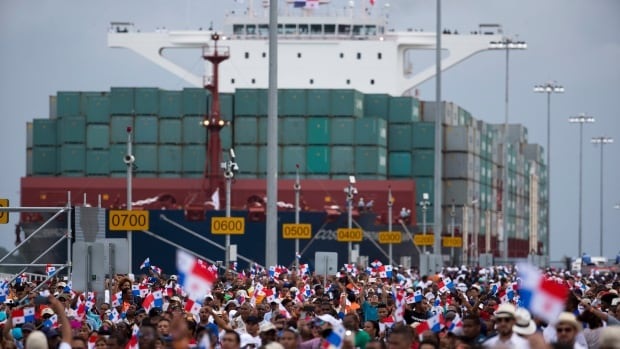 Thousands of people  watched as the Neopanamax cargo ship, Cosco Shipping Panama, made its way through the new Agua Clara locks, part of the Panama Canal expansion project, near the city of Colon on Sunday.
