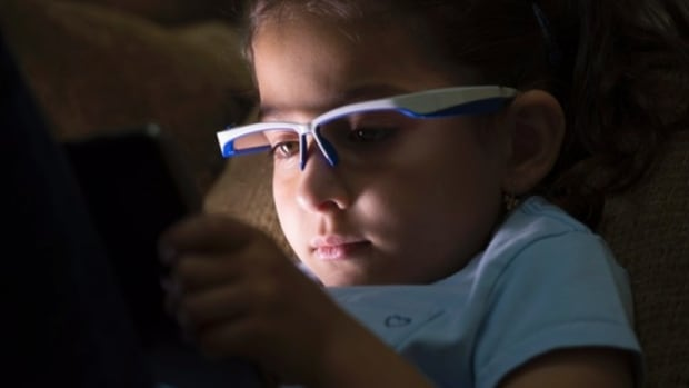 Liliya Sahiholnasab uses the special glasses to remind her to correct her posture when using a tablet at her home in Richmond, B.C.