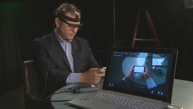 Reporter Aaron Saltzman wears brain-monitoring equipment while browsing online shopping sites on a smartphone.