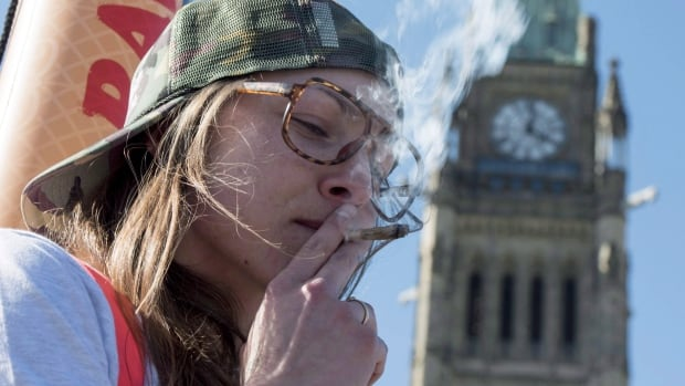 A woman smokes a joint during the annual 4/20 marijuana rally on Parliament Hill on April 20, 2016, in Ottawa. Prime Minister Justin Trudeau campaigned on a promise to legalize, regulate and restrict access to marijuana, and his government plans to get started next spring.