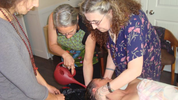 "Death midwife Pashta MaryMoon (far right) instructs others on a live model, how to properly wash and care for a dead body at home. The College of Midwives of British Columbia says the title ""midwife"" is protected by law and has sent a cease and desist letter to MaryMoon's organization ordering them to stop using it."