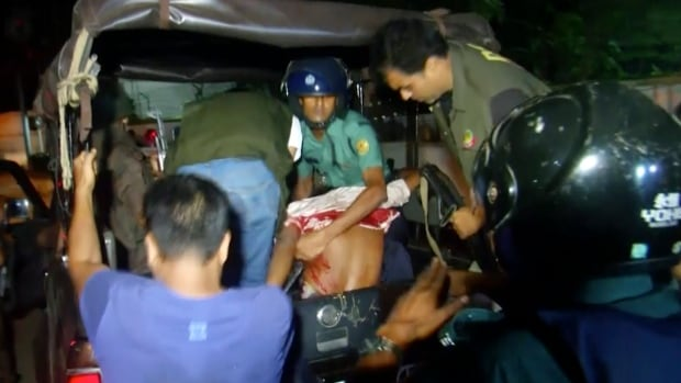An injured man who escaped from the Holey Artisan Bakery in Dhaka is loaded onto a truck.