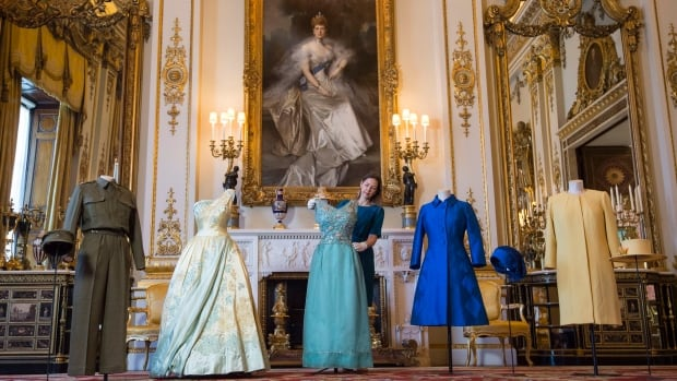 "Curator Caroline de Guitaut adjusts displays during a press preview for ""Fashioning a Reign: 90 Years of Style from The Queen's Wardrobe"", an exhibition at Buckingham Palace in London, Monday July 4, 2016. An unprecedented peek into Queen Elizabeth's royal wardrobe is taking place this summer at Buckingham Palace. (Lauren Hurley/PA via AP)"