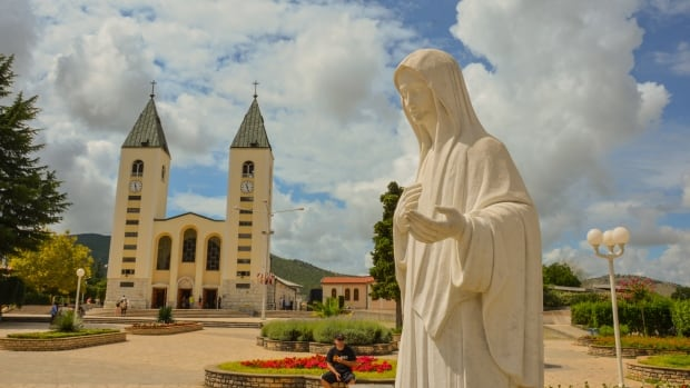 A church and a statue of the Virgin Mary in Medjugorje, Bosnia-Herzegovina - the setting for a new documentary that includes a Nova Scotian man.