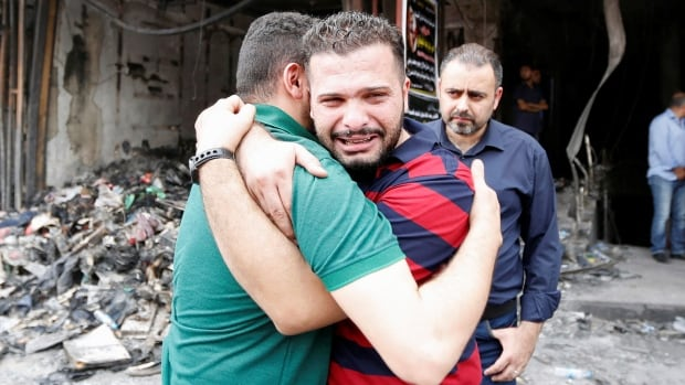 Iraqi men react on July 4 at the site after a suicide car bomb attack at the shopping area of Karrada, a largely Shia district, in Baghdad.