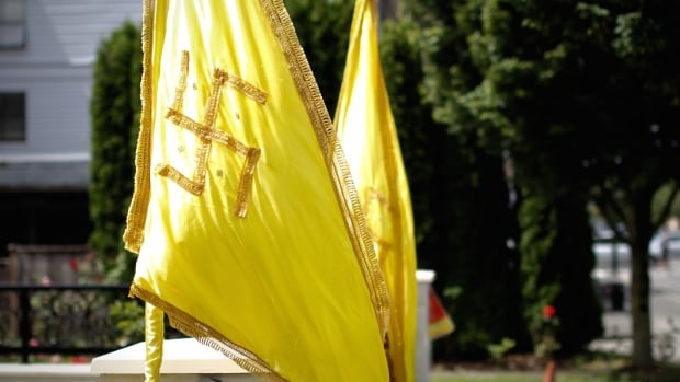 Two large yellow flags with swastikas fly in front of a Vancouver home. The homeowner says they have nothing to do with Adolf Hitler and the Nazis. The symbol has been used by various religions for centuries.