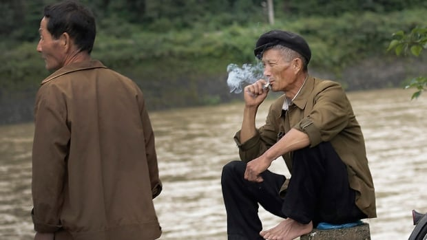 North Korean men sit and smoke by a river in the North Pyongan Province. The  country where just about every adult male can and does light up almost anywhere he pleases is now officially trying to get its people to kick the habit.