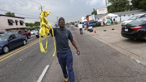 Raymond Gregory holds up crime scene tape, encouraging motorists to honk, outside the Triple S convenience store in Baton Rouge, La. Alton Sterling, 37, was shot and killed outside the store by police, where he was selling CDs.