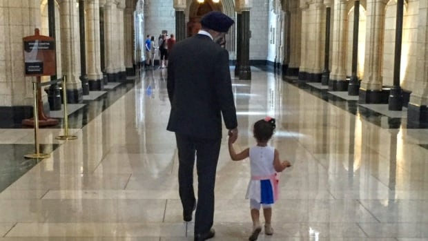 Defence MInister Harjit Sajjan held Sophia Popalyar's hand as they walked through the halls of Parliament together during a special tour.