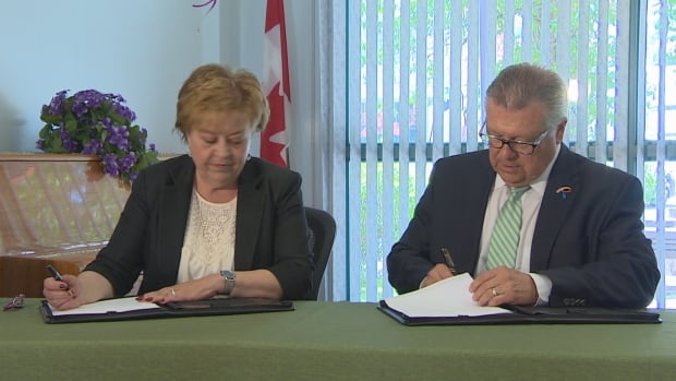 Donna Harpauer and Ralph Goodale sign an agreement to shore up funding for affordable and social housing in Saskatchewan.