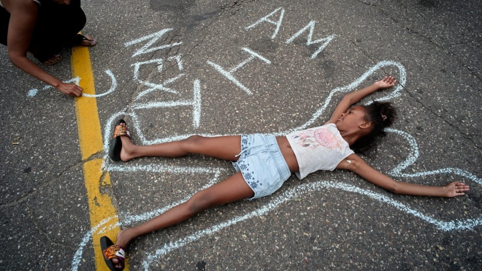 Tia Williams, left, and her daughter Aissa create a display on the street outside the Minnesota governor's official residence to protest the shooting death of Philando Castile by police.
