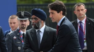 Prime Minister Justin Trudeau arrives with Defence Minister Harjit Singh Sajjan, centre, at the NATO summit in Warsaw last summer. In something of a surprise, the 2017 federal budget kicks a further $8.5 billion in defence procurement spending many years down the road.