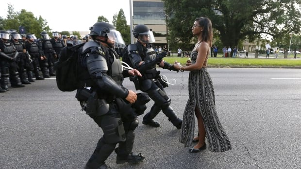 A demonstrator protesting the shooting death of Alton Sterling is detained by law enforcement near the