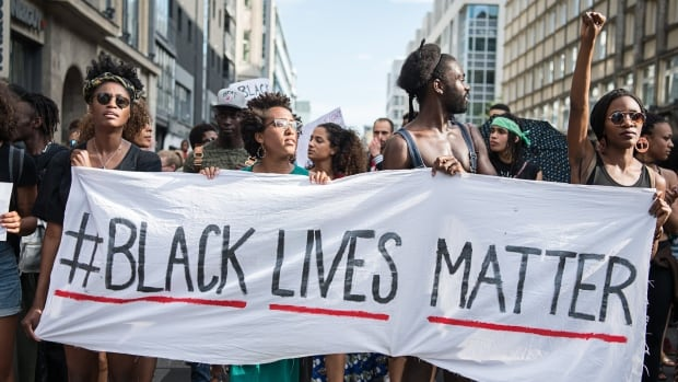 Protesters hold a banner during a demonstration in Berlin, on July 10, as protest over the deaths of two black men at the hands of police.