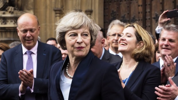 Theresa May is applauded by fellow Conservative Party members of parliament outside the Houses of Parliament in London, on Monday, after it was confirmed she would be the party's new leader. An underwear model with a similar name has been mistaken for May online.