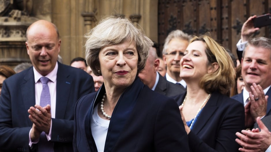 """Britain's Theresa May is applauded by Conservative Party members of parliament outside the Houses of Parliament in London, Monday July 11, 2016. Britain's Conservative Party has confirmed that Theresa May has been elected party leader """"with immediate effect"""" and will become the country's next prime minister."""