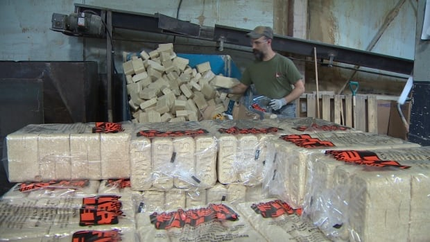 A worker bags Fiber Fuel bricks at Lewis Mouldings in Weymouth, N.S. The home-heating alternative is popular enough that the company is expanding for the second straight year.