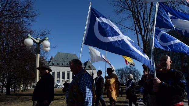 Métis leaders carry the Métis flag while marching to the Supreme Court of Canada in Ottawa on April 14, 2016, when the top court ruled in favour of Métis and non-status Indians in the Harry Daniels case.
