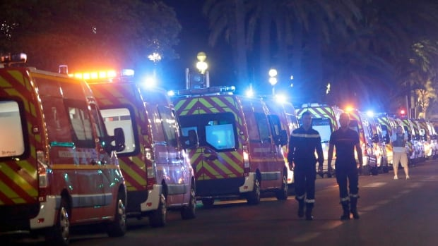 Ambulances line up near where a truck drove on to the sidewalk and plowed through a crowd of revellers who'd gathered to watch the fireworks in the French resort city of Nice in southern France.