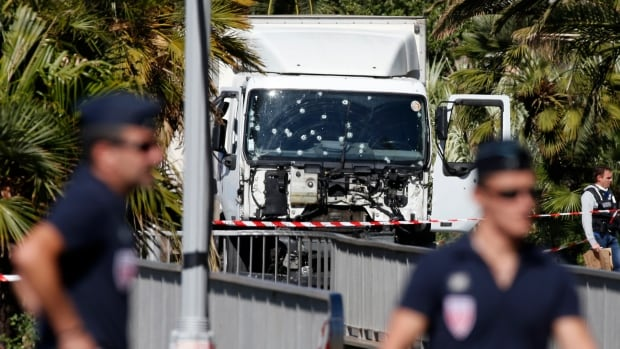 French police secure the area as the investigation continues at the scene near the heavy truck that ran into a crowd at high speed killing scores who were celebrating Bastille Day.