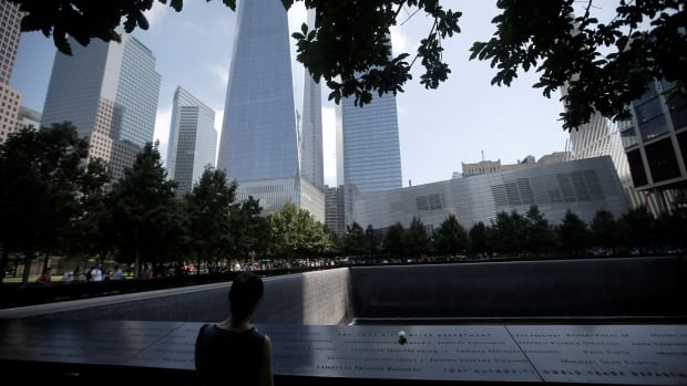 A single white rose is left at the edge of the South Pool of the 9/11 Memorial in New York.