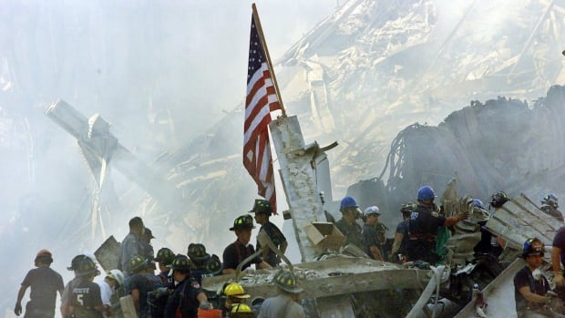 An American flag flies over the rubble of the collapsed World Trade Center buildings in New York in this 2001 file photo.