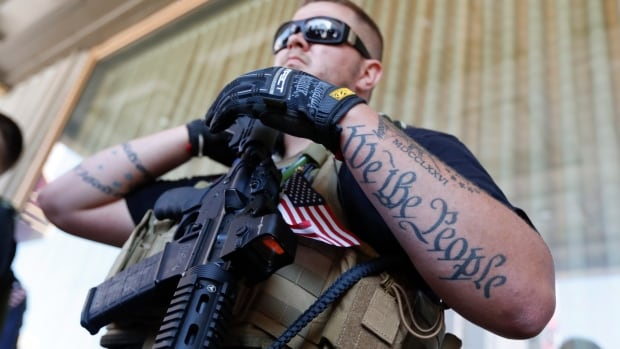 Tevor Leis, exercising his Ohio open-carry rights, stands armed in Public Square on July 19, 2016, in Cleveland, during the second day of the Republican National Convention.