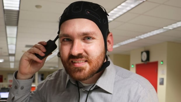 Neuroscientist Matthew Krause wears a portable transcranial direct current stimulation kit. He cautions against trying tDCS at home because the procedure is still in the experimental stages and enough is not known about its effects.