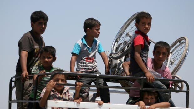 Boys on a pick-up truck evacuate from the southern districts of Manbij city after the Syria Democratic Forces fighters advanced into it on July 1. Airstrikes on the ISIS stronghold have killed scores of civilians, including children, rights groups allege.