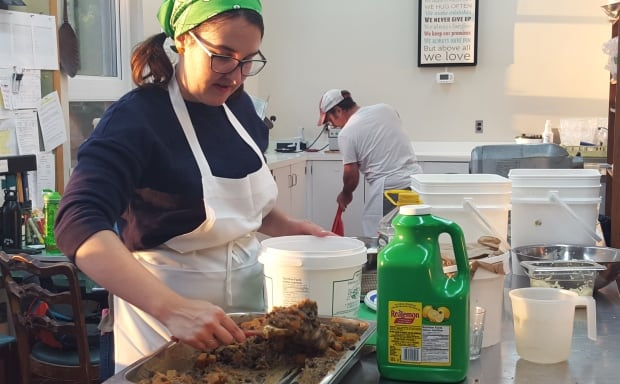 Volunteer scoops black bean sweet potato mix Hillside Festival food prep