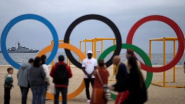 A Brazilian naval ship patrols the coast as people pose with the Olympic rings in Rio de Janeiro on July 21, 2016. Researchers estimated that the probability of a person visiting Rio and getting infected with Zika ranges from one in 6,200 to one in 56,300, which translates to a total of six to 80 Zika infections.