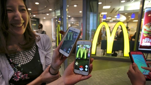 Women play Pokemon Go in front of a McDonald's restaurant in Tokyo on Friday, where the app's launch broke new ground by forging a corporate partnership.