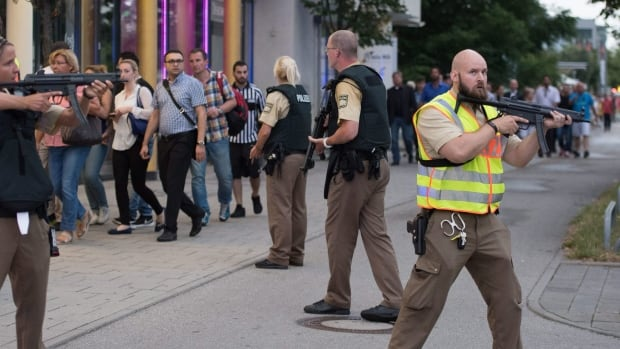 Police escort people who leave the Olympia mall in Munich, southern Germany on Friday.