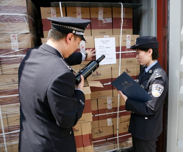 Chinese customs officers inspect boxes labelled with Lulu Island Winery logo