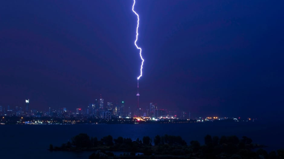 A lightning bolt strikes the CN Tower in Toronto as heavy winds and rain batter the city and cause delays for people trying to get around on July 25, 2016.