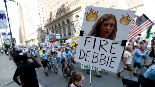 A supporter of Senator Bernie Sanders holds up a sign on Sunday in Philadelphia, calling for Debbie Wasserman Schultz, chairwoman of the Democratic National Committee to be fired. Schultz did announce her resignation Sunday evening amid controversy over leaked emails from the DNC.