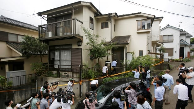 Members of the media crowd outside as police officers raid the house of Satoshi Uematsu, suspected of killing 19 people in a facility for the disabled.