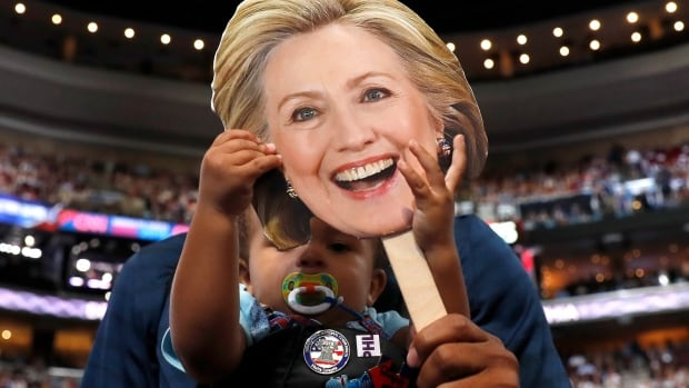 Ethan Jennings, 16 months old,  grabs a cardboard cutout of the face of Democratic presidential candidate Hillary Clinton as his father, Florida delegate Bernard Jennings, holds him on Tuesday at the Democratic National Convention. Ethan is a bit young to vote this time around, but millennials will be a big voting bloc in November.
